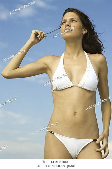 Woman in bikini standing holding strand of hair, looking away