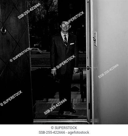 Man wearing suit standing in doorway of house