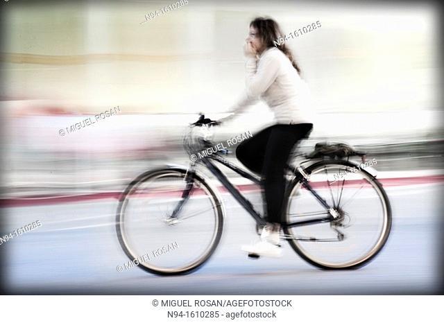 Young woman biking through the city