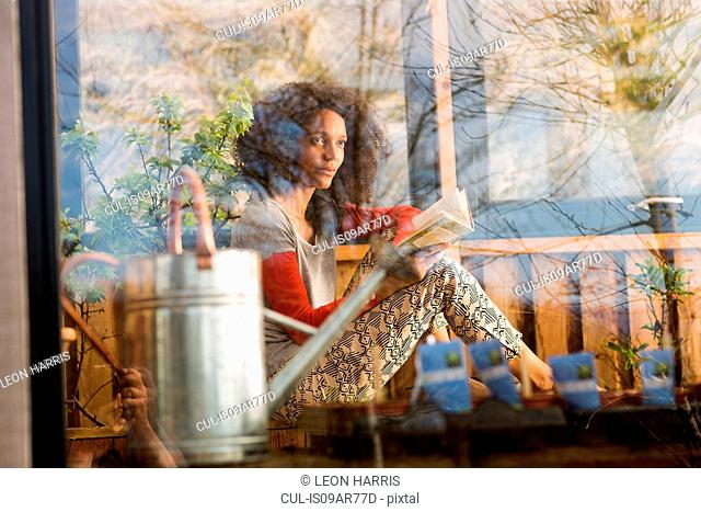 Woman reading a book, view through window