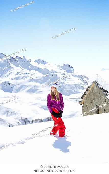 Young woman walking through snow