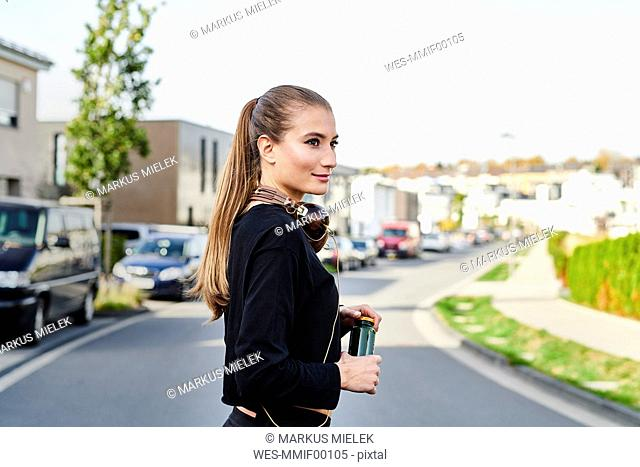 Smiling sportive young woman on a street in the city
