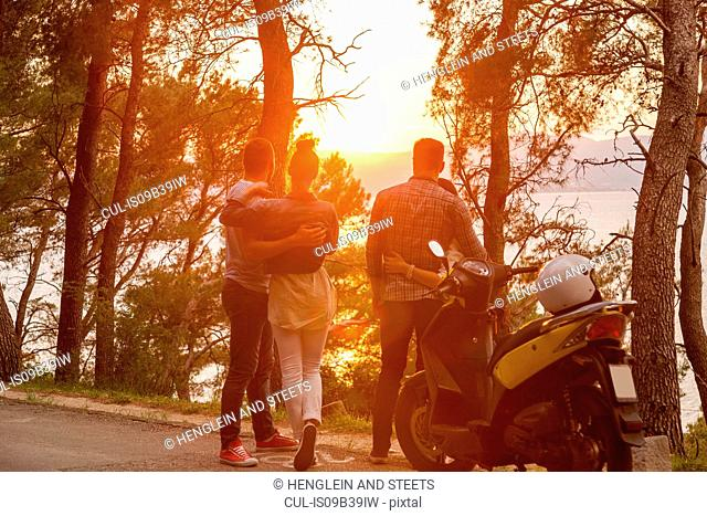 Two moped couples looking out at sunset from coastal road, Split, Dalmatia, Croatia