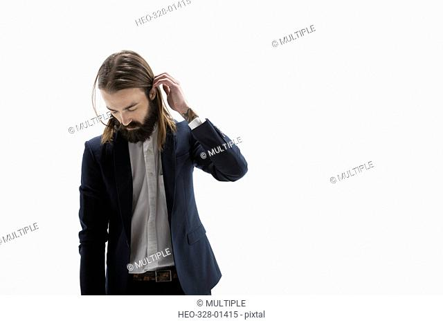 Cool businessman with beard looking down against white background