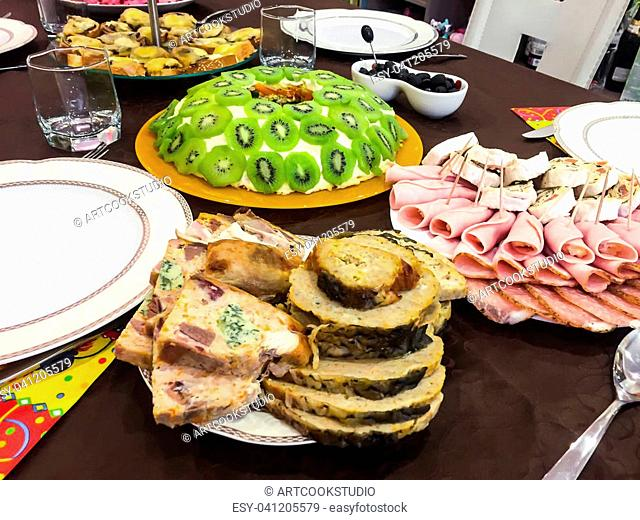 Salad with kiwi, ham, pieces of stuffed turkey, rolls with salmon at a Christmas dinner. Studio Photo