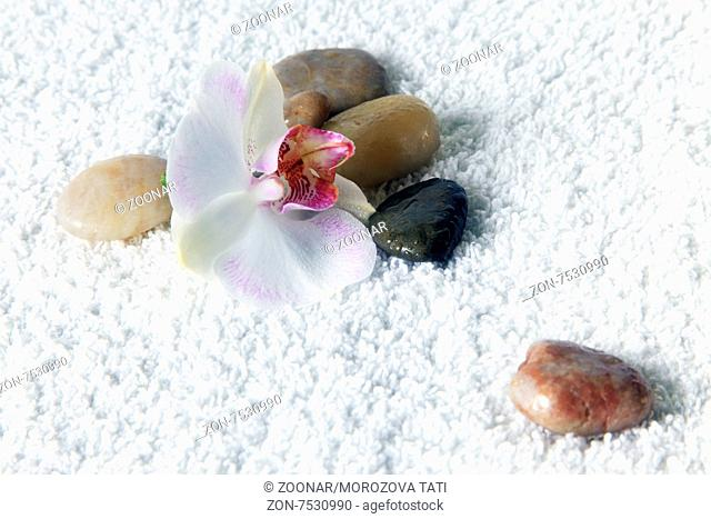 Stones for massage and an orchid on a white towel