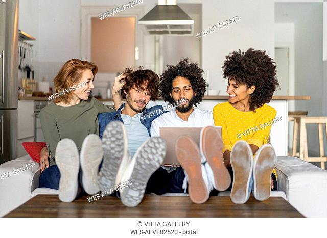 Friends sitting on couch, watching laptop