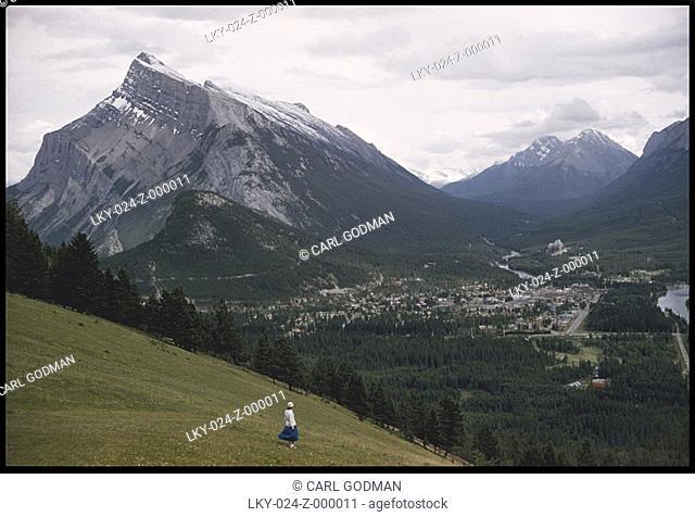 Woman walks down hilly region of mountain range