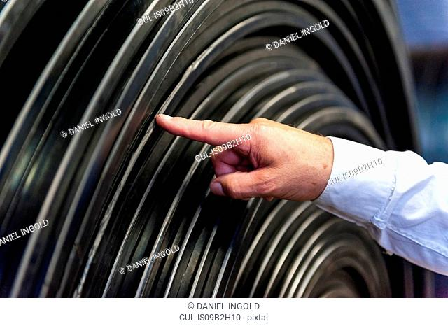 Male worker checking roll of rubber in rubber roller factory, close-up