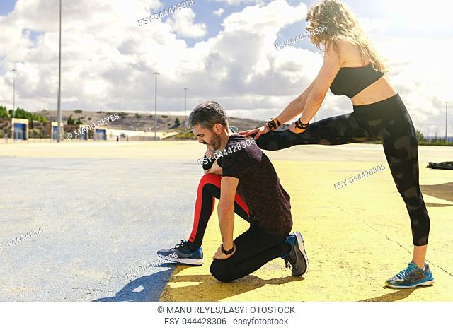 young couple stretching together before running outdoors