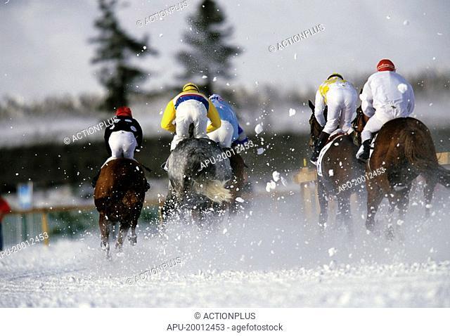 Group of jockeys racing their horses across an snow circuit