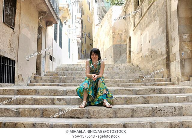 Mid adult woman in summer dress sitting on stairs