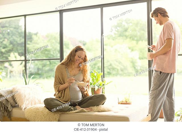 Pregnant couple eating and drinking coffee in living room