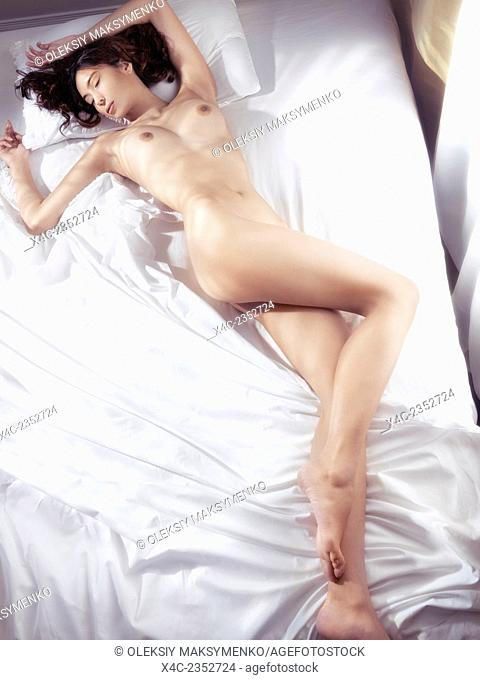 Beautiful young woman sleeping naked in bed with bright morning sunlight coming from the window