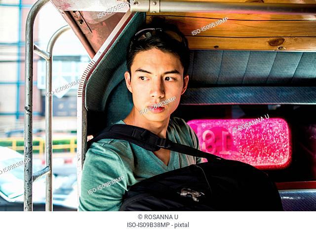 Young man sitting in back of tuk tuk, Chiang Mai, Thailand
