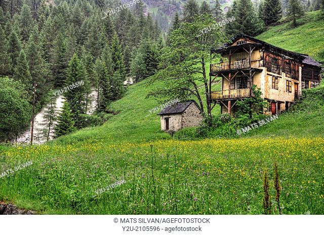 Old house close to a waterfall on the green field with flowers in Switzerland