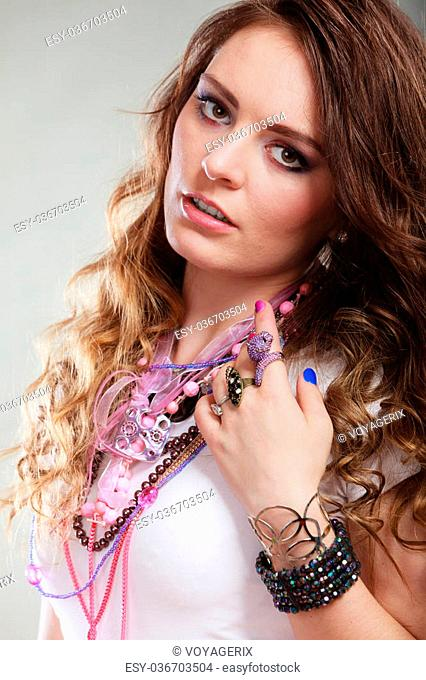 Pretty young woman wearing many plenty of jewelry necklaces beads, rings and bracelets. Portrait of gorgeous fashion girl in studio on gray