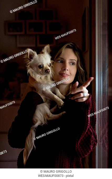 Woman standing beside window with her dog pointing on something