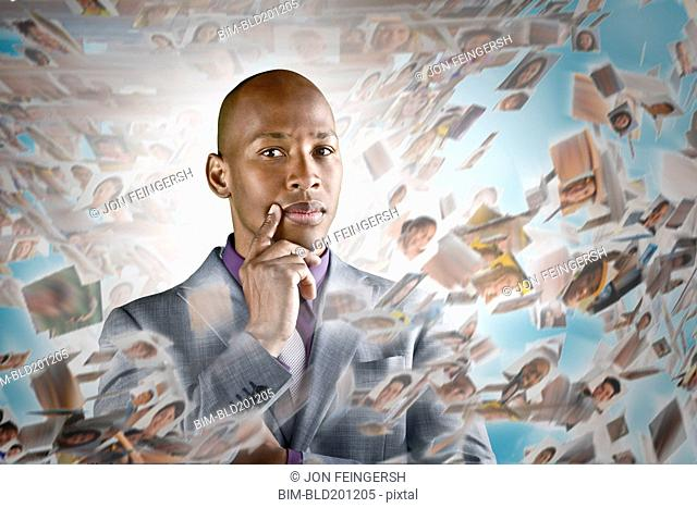 African American businessman surrounded by images of business people