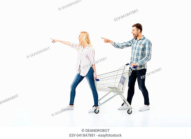 Full length portrait of a happy couple standing with a shopping trolley and pointing away isolated over white background