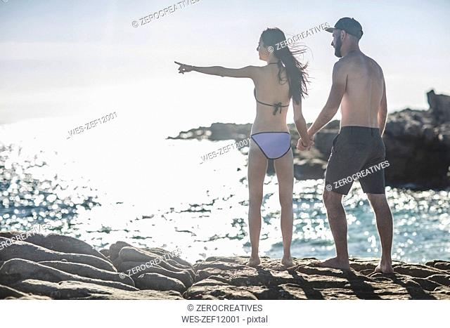 Young couple looking at view on the beach