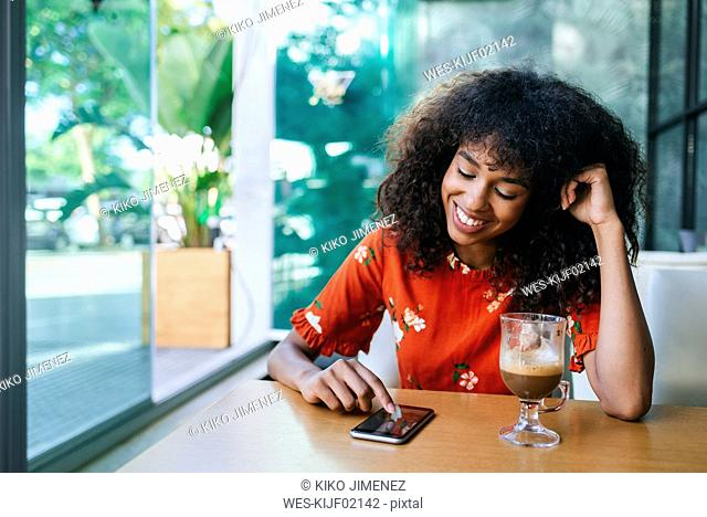 Portrait of smiling young woman in coffee shop using cell phone