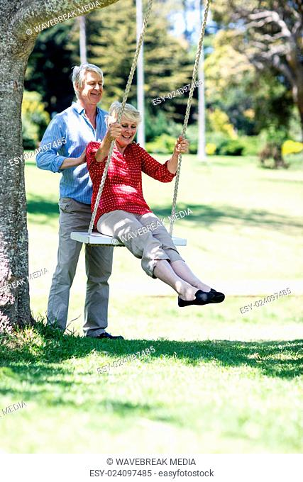 Senior man pushing his partner on swing