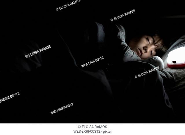 Girl sleeping in bed at night with night light