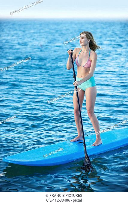 Young woman in bikini paddleboarding on summer ocean