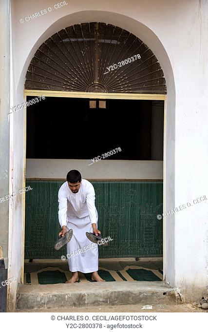 Ksar Elkhorbat, Morocco. Man Removing Shoes before Entering Mosque