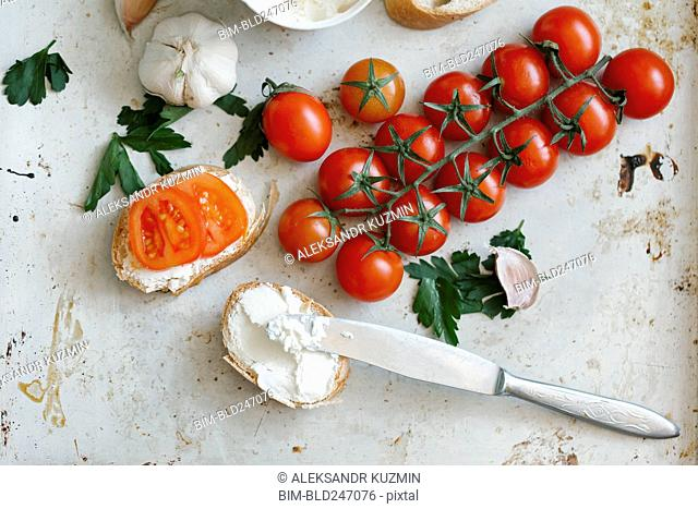 Tomatoes on vine near cream cheese and bread