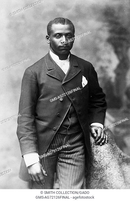 Sepia studio portrait of an African-American man, three quarter length, dressed in jacket, vest, tie and striped pants, 1900