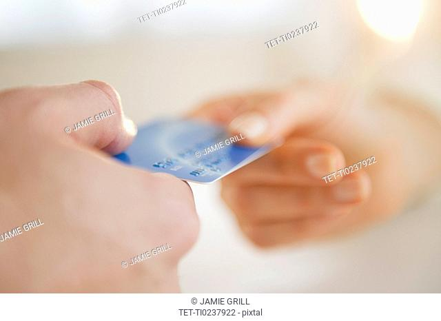 Close up of man's and woman's hands holding credit card