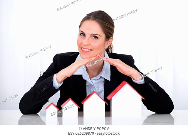 Portrait Of Happy Businesswoman Protecting House Models In Office