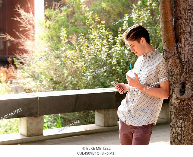 Young man outdoors, leaning against tree, using smart phone, holding takeaway cup