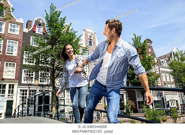 Netherlands, Amsterdam, happy couple running hand in hand on a bridge
