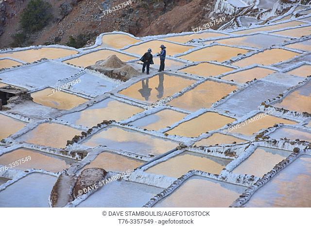 Sunset reflections on the salt pans of Maras, Sacred Valley, Peru