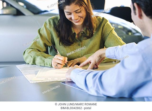 Woman signing contract at car dealership