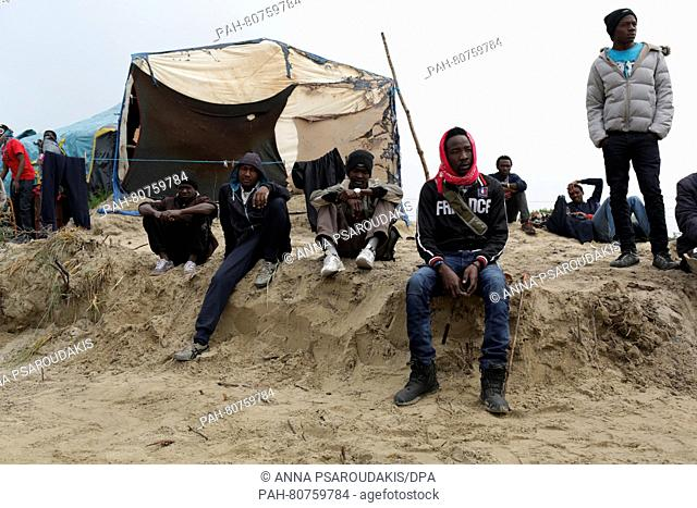 Sudanese men contemplate the burned landscape in the migrant camp dubbed the 'Jungle' on the outskirts of Calais, France, 27 May 2016
