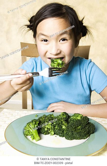 Young Asian girl eating broccoli