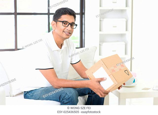 Courier delivery concept. Indian guy received an express parcel and checking the box at home. Handsome male portrait. Asian man sitting on sofa indoor