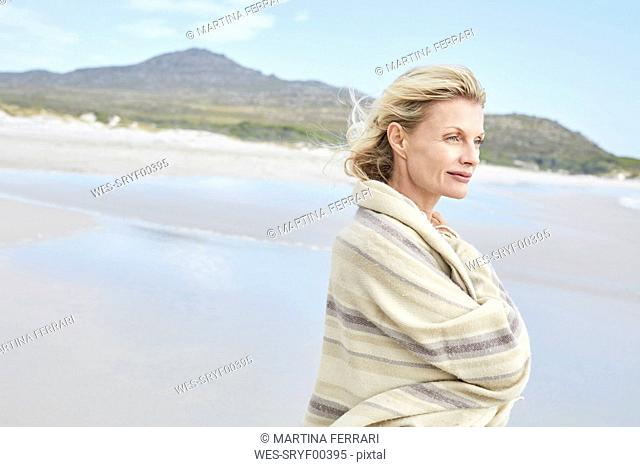 Mature woman enjoying the sea, wrapped in a blanket