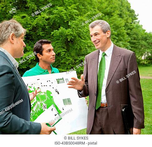 Businessmen talking in park