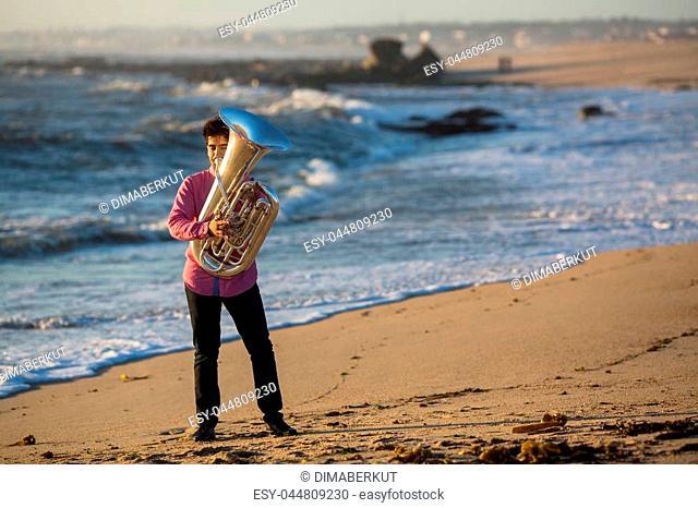 Musician play to Tuba on romantic sea shore