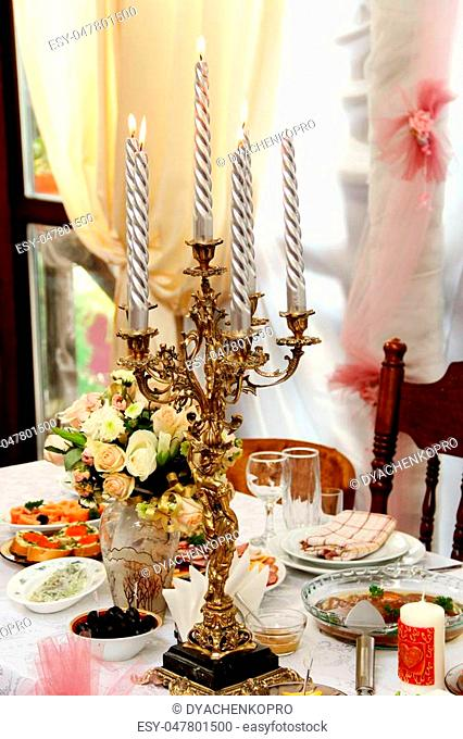 candlestick with large silvery candles on the festive table fire