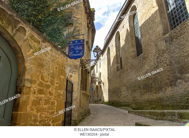Hotels in medieval sandstone buildings on narrow cobblestone street in charming Sarlat, in Dordogne region of France