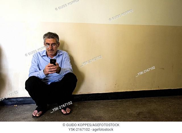 Harmanli, Bulgaria. Male Syrian refugee, kneeled against a residential wall, using his smartphone to retrieve information from the internet