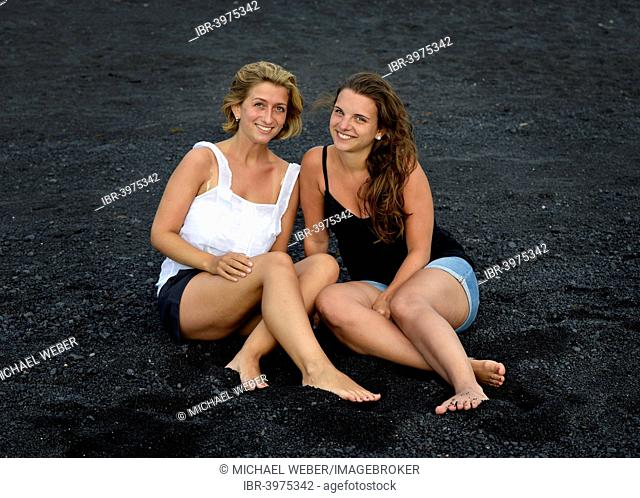Two young women, girlfriends, on a black lava beach, Lanzarote, Canary Islands, Spain