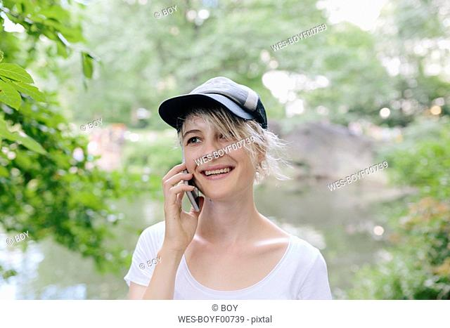 Smiling young woman in park talking on cell phone