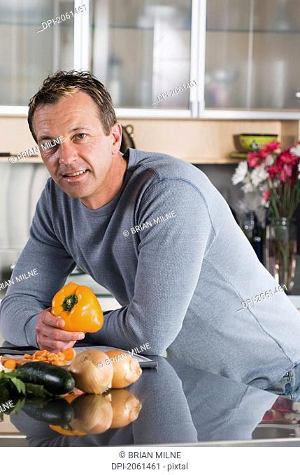 Man With Vegetables In Kitchen, Winnipeg, Canada